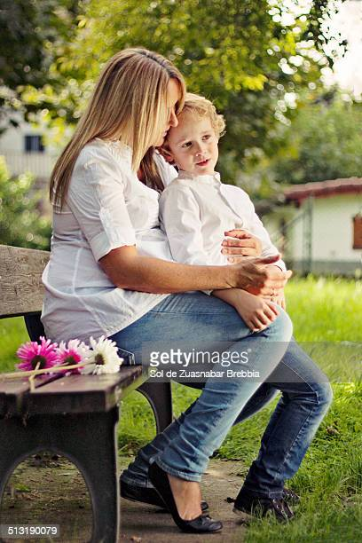 pregnant mother and her son sitting on a bench - mom sits on sons lap stock pictures, royalty-free photos & images