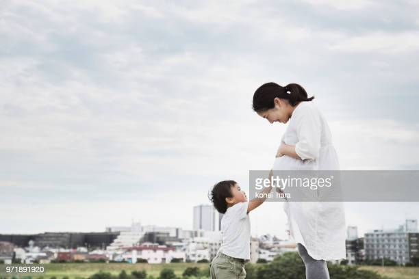 Pregnant mother and son relaxed on the hill