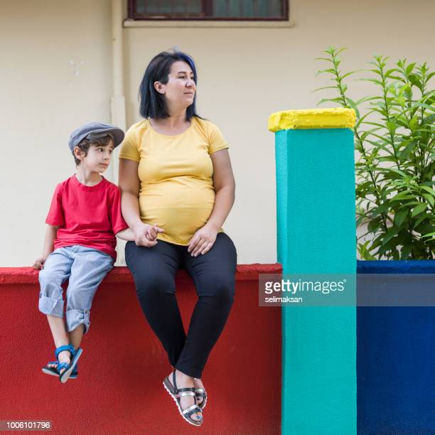 Pregnant Mother And Son Sitting On Multi Colored Wall