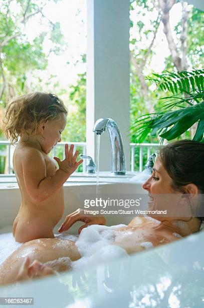 pregnant mother and toddler in bath - menina infancia pelada banheira imagens e fotografias de stock