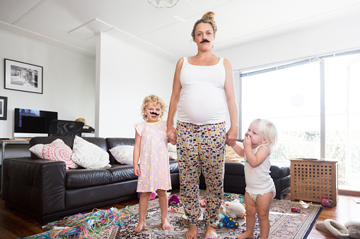 Pregnant mother and two children wearing moustaches in messy living room - gettyimageskorea