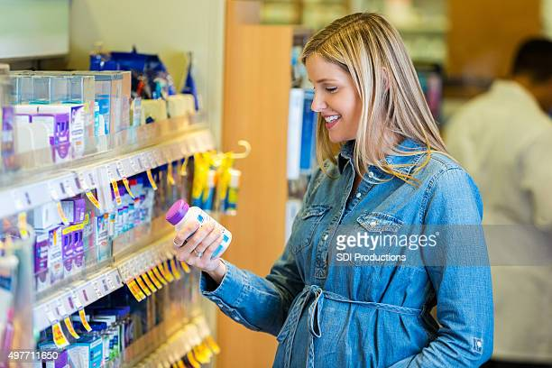 Pregnant mother reading prenatal vitamin label in pharmacy