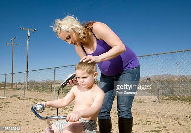 pregnant mother shaving her son's head - redneck woman stock photos and pictures