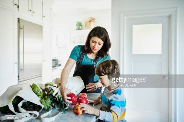 pregnant mother showing young son apples in kitchen after shopping for groceries - family with one child stock pictures, royalty-free photos & images
