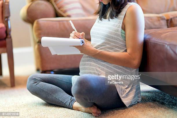 Pregnant mother sitting on carpet using a pad and paper