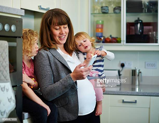 Pregnant mother using smartphone with daughters