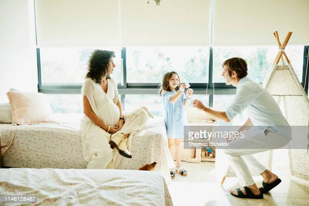 pregnant mother watching father and young daughter play in bedroom - マタニティウェア ストックフォトと画像