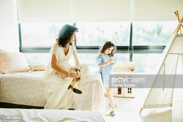 Pregnant mother watching young daughter admire toy in bedroom