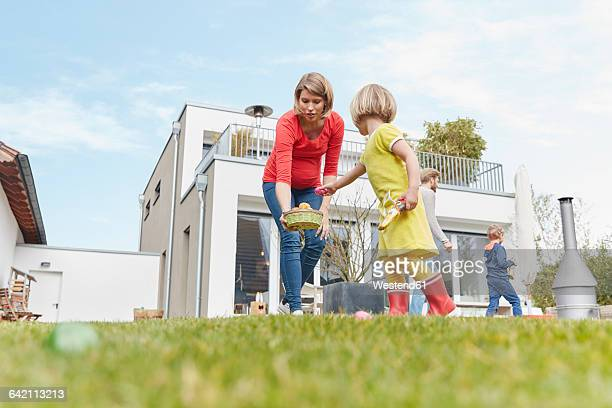 Pregnant mother with children in garden looking for Easter eggs