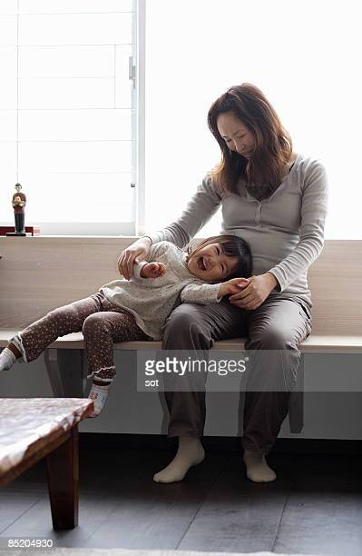Pregnant mother with daughter,smiling