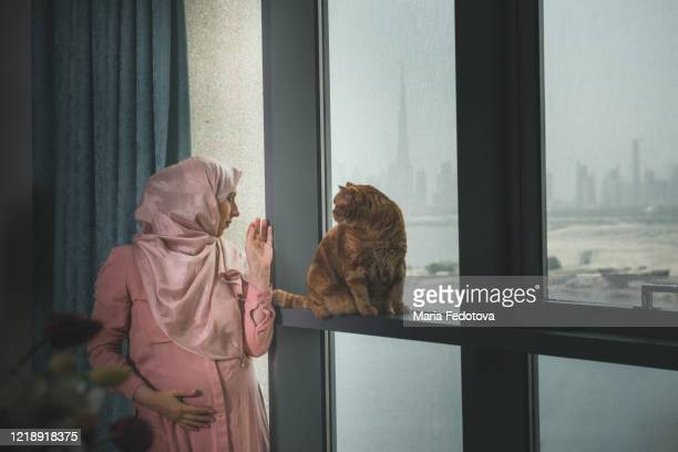 pregnant muslim woman standing near the window - coronavirus uae stock pictures, royalty-free photos & images