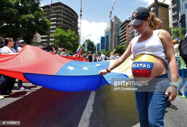 A pregnant opposition activist with the word 'Freedom' written on her belly takes part in a demonstration marking 100 days of protests against...