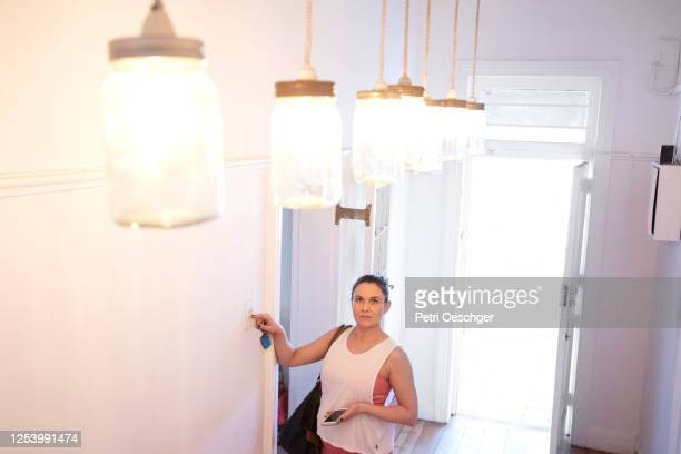 a pregnant pilates instructor turning on the lights at her studio. - turning on or off stock pictures, royalty-free photos & images