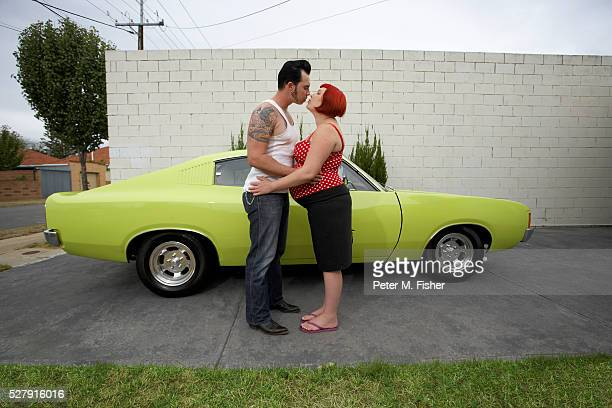 Pregnant Rockabilly Couple Kissing by Muscle Car