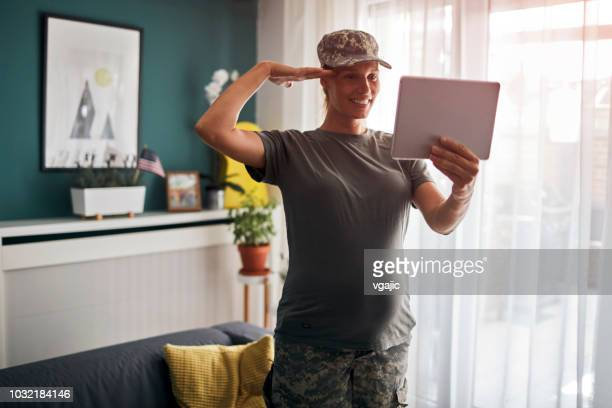 pregnant service woman at home - saluting stock pictures, royalty-free photos & images