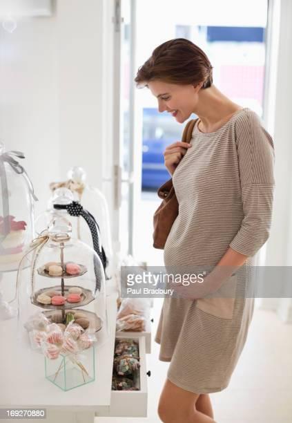 Schwangere Frau Genießen Sie cookies in store