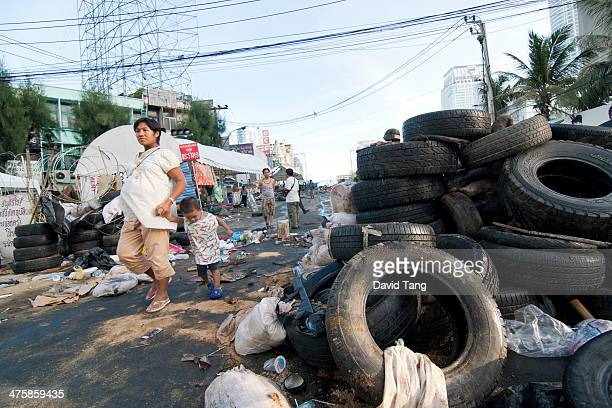 Pregnant woman and child is walking through the remains of an anti-government occupied area during the 2010 Bangkok Riots.