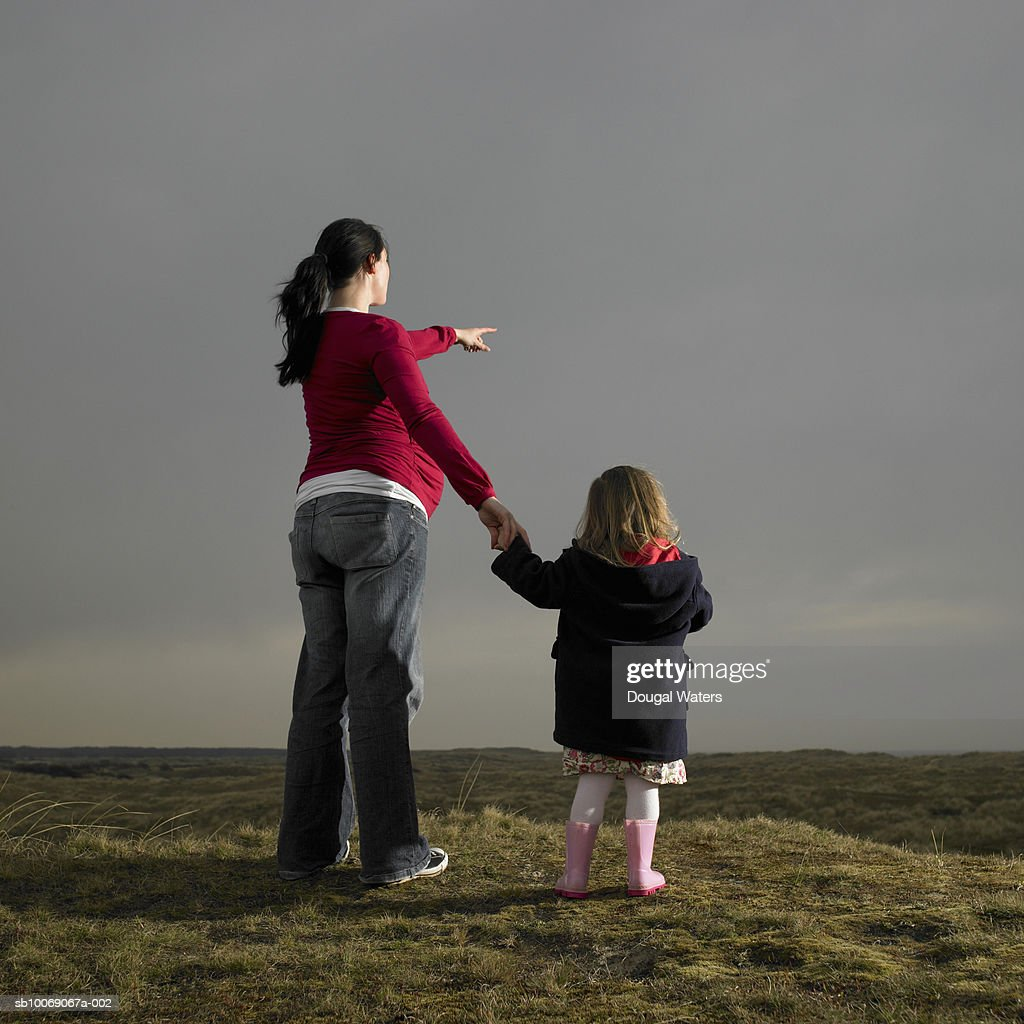 Pregnant woman and daughter (2-3) standing on heath land, rear view : Stockfoto