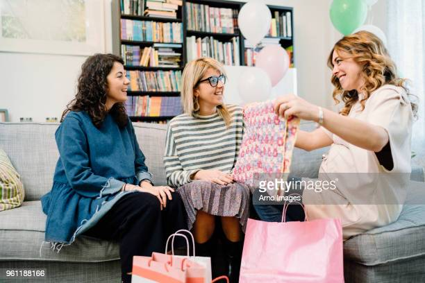 pregnant woman and friends on sofa admiring baby blanket - baby shower stock photos and pictures