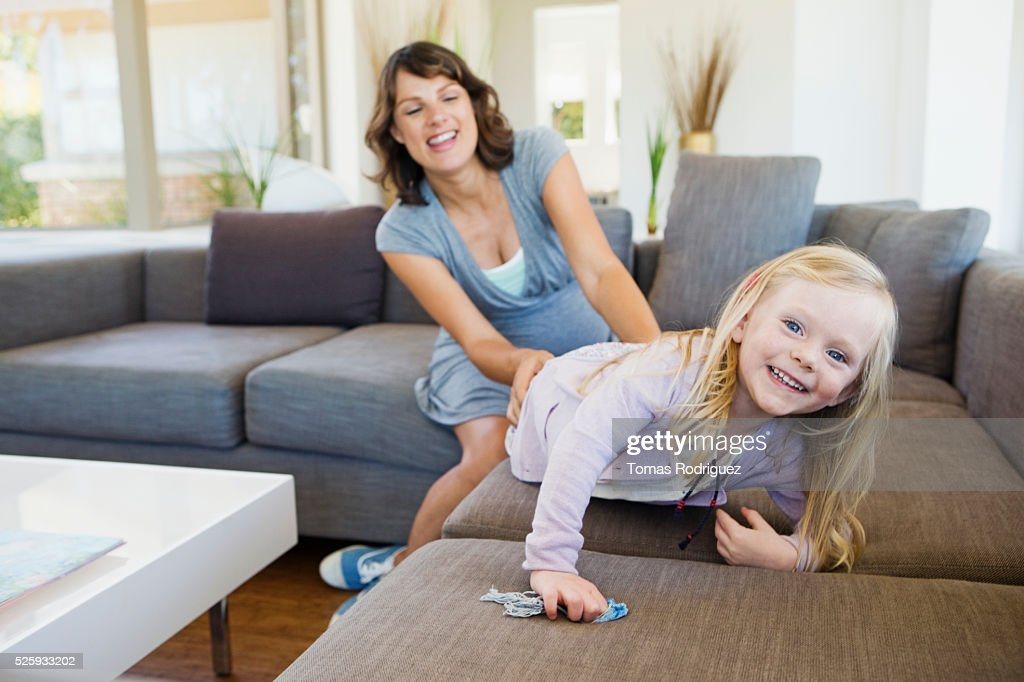Pregnant woman and girl (2-3) playing in living room : Stock Photo