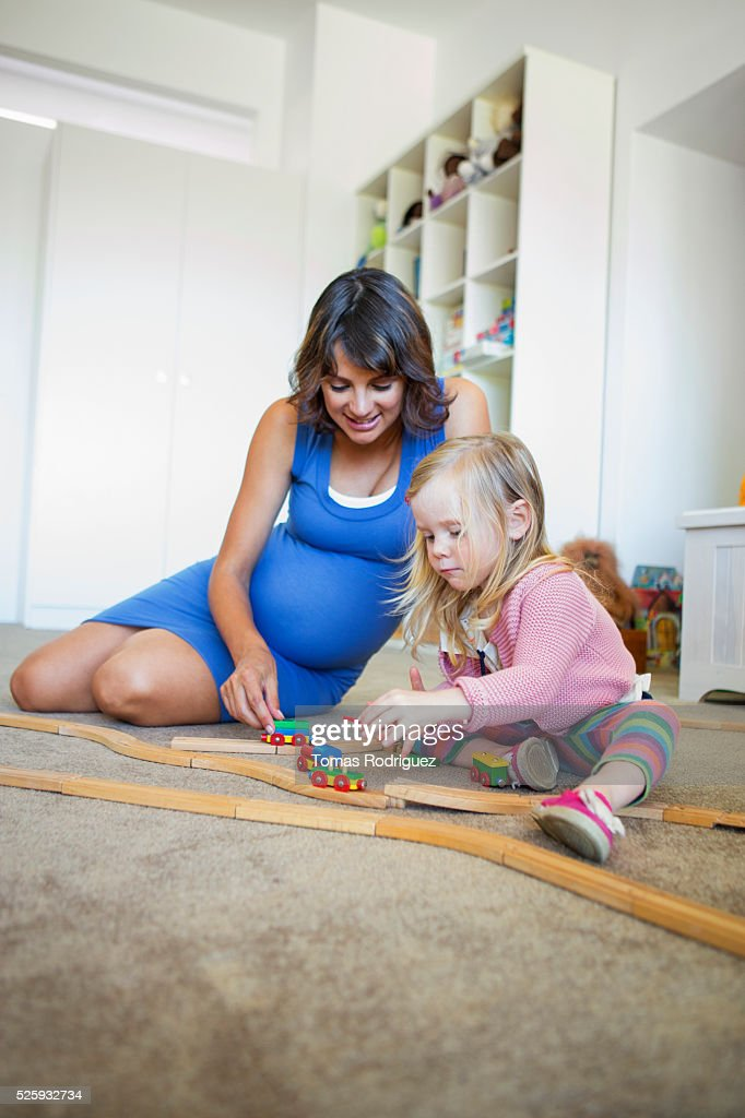 Pregnant woman and girl (2-3) playing with toy train : Bildbanksbilder