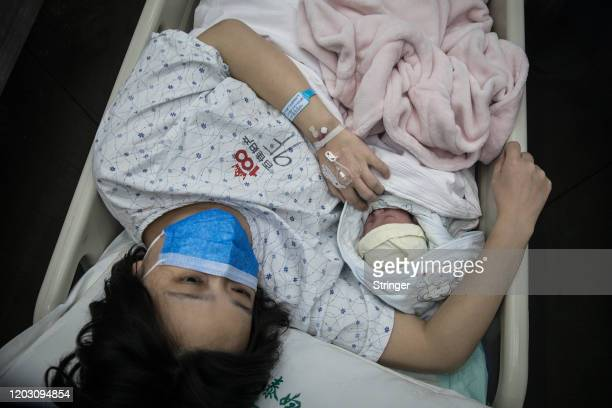 Pregnant woman and her newborn baby are transferred by a nurse on February 21, 2020 in Wuhan, Hubei, China. Due to the shortage of medical resources...
