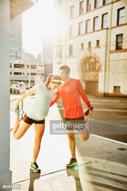 Pregnant woman and husband using each other for balance while stretching before early morning run in city