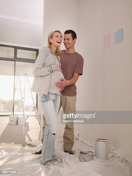 Pregnant woman and man painting nursery