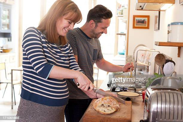 Pregnant woman and partner cooking together