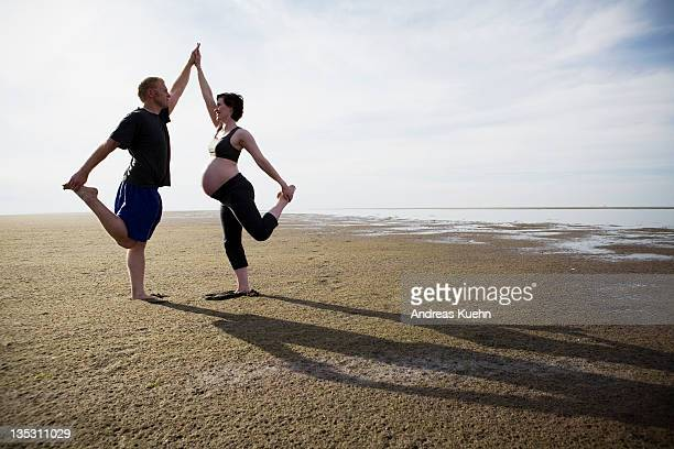 Pregnant woman and partner doing yoga on beach.