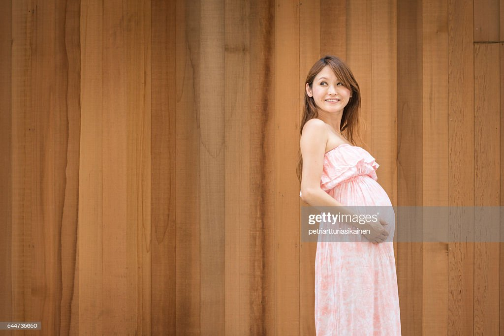 Pregnant woman and wooden wall. : Stock Photo