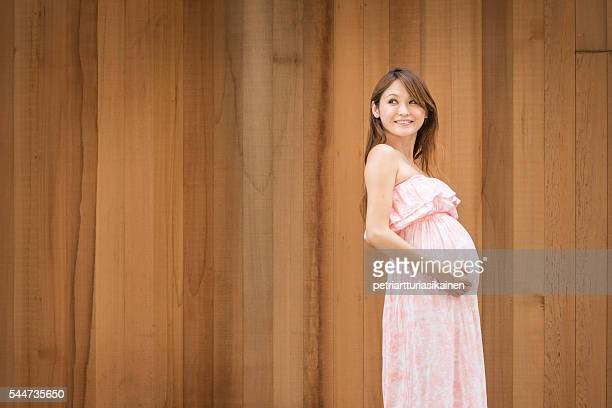 Pregnant woman and wooden wall.