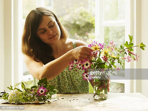 Pregnant woman arranging flowers in glass vase