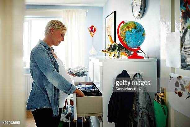 Pregnant woman arranging the wardrobe