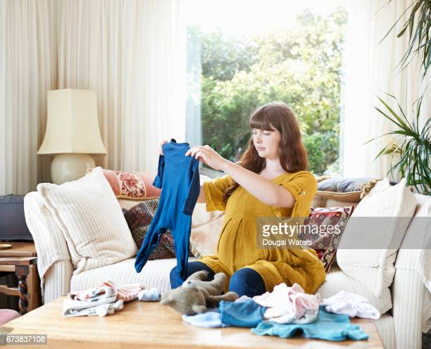 Pregnant woman at home looking at baby clothes.