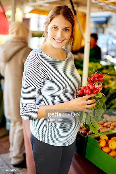 Pregnant woman at market holding radishes