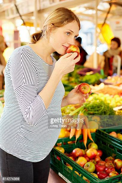 Pregnant woman at market smelling apples