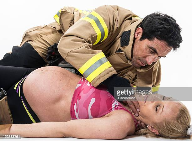 Pregnant woman being help by a fireman