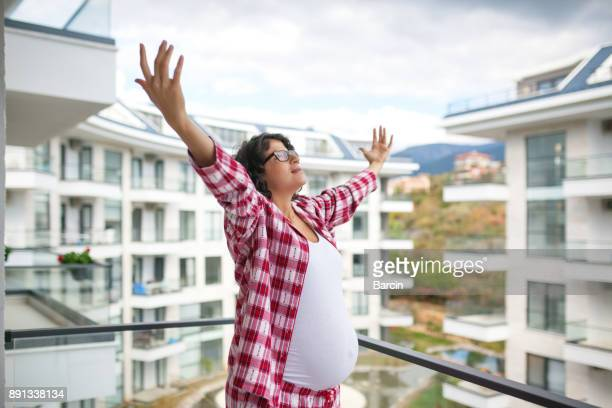 Pregnant woman breathing deep fresh air in a balcony