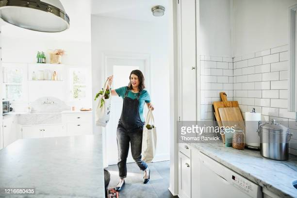 pregnant woman bringing groceries in canvas bags into kitchen - arrival stock pictures, royalty-free photos & images