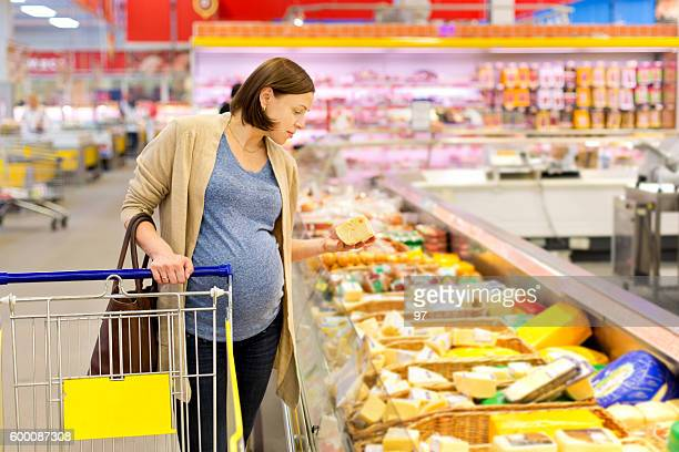 pregnant woman buys cheese in the supermarket