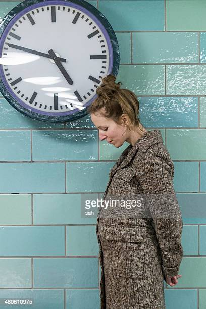 Pregnant woman by clock
