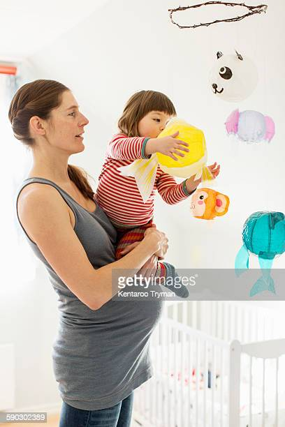 Pregnant woman carrying girl playing with toy in baby room