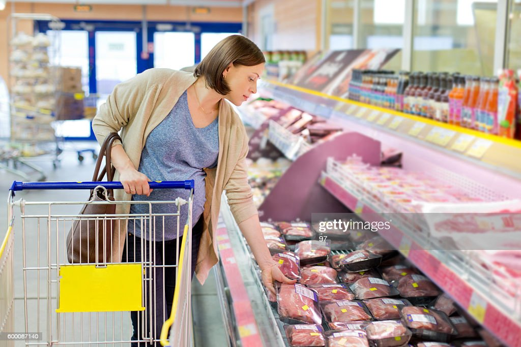 pregnant woman chooses meat in the store : Stock Photo