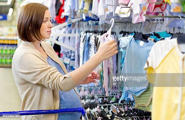 pregnant woman choosing newborn clothes at baby shop