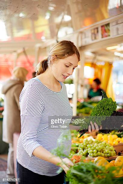 Pregnant woman choosing vegetables at market