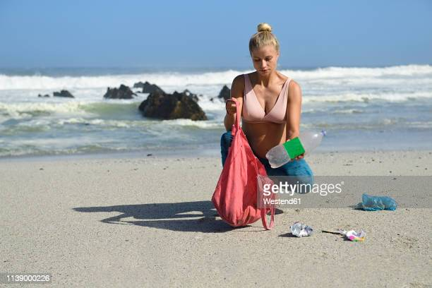 pregnant woman cleaning the beach from plastic waste - moment collection stock pictures, royalty-free photos & images