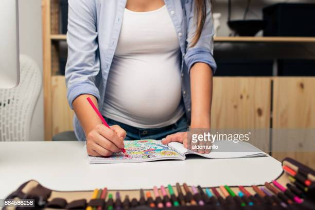 Pregnant woman coloring a coloring book