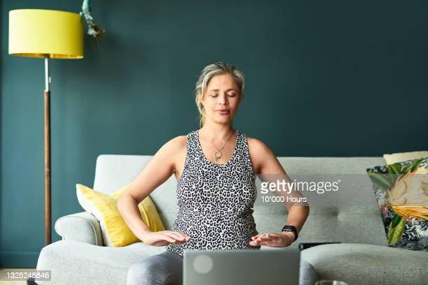 pregnant woman concentrating on breathing exercises sitting on sofa - one mature woman only stock pictures, royalty-free photos & images