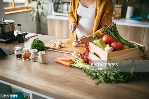 schwangere frau schneidet pilze ab - speisen und getränke stock-fotos und bilder